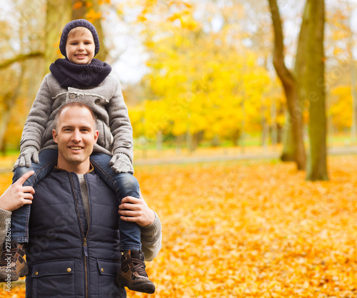 family, childhood, season and people concept - happy father and son having fun in autumn park