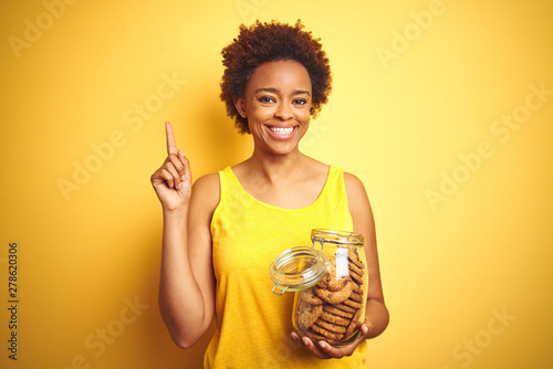 Obraz na plátně  African american woman holding jar of chocolate chips cookies over yellow backgr