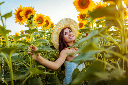 Poster Melon Young woman walking in blooming sunflower field feeling free and admiring nature. Summer vacation