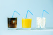 Leinwanddruck Bild - Excessive sugar consumption concept - cola, juice and sugar cubes in glasses on blue background, copy space