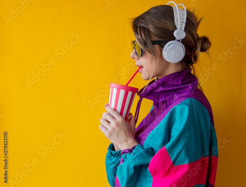 Photo sur Aluminium Magasin de musique Young woman in 90s style clothes with cup and headphones