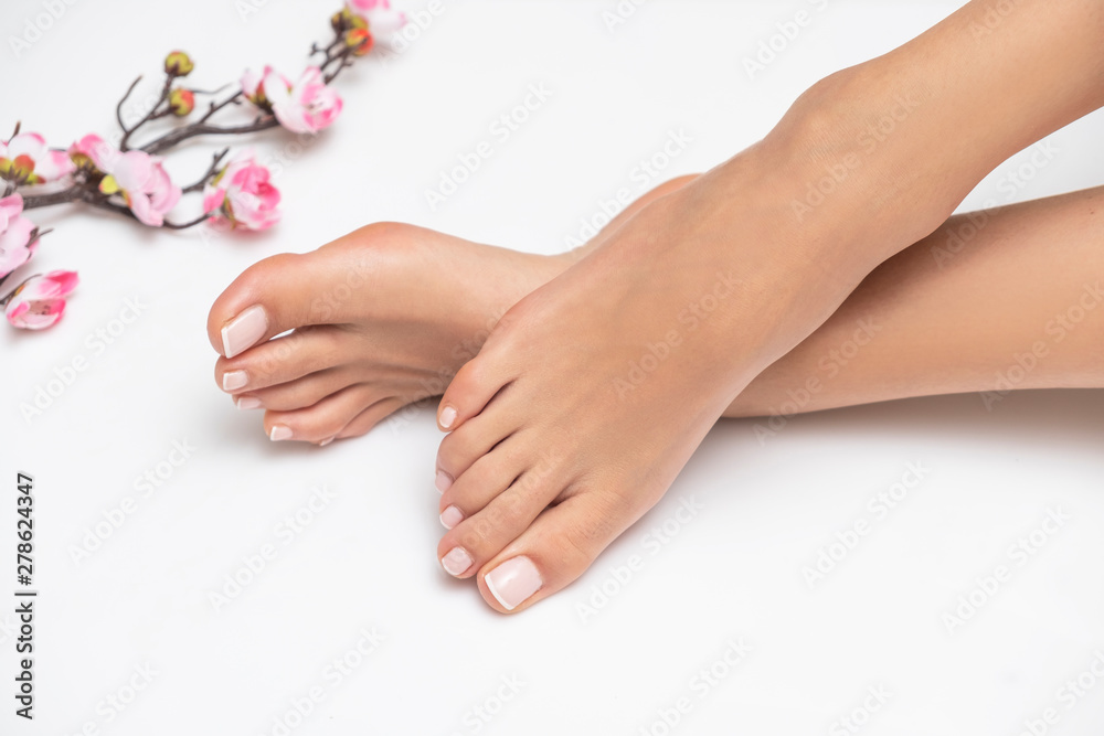 Fototapeta Perfectly done french pedicure on white background.