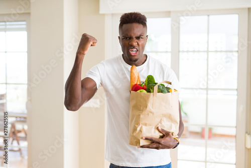 African american man holding paper bag full of fresh groceries annoyed and frust Canvas-taulu