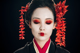 portrait of beautiful geisha with flowers in hair isolated on black
