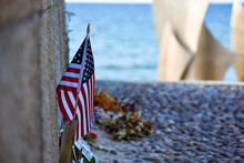 United States Flag, Flowers And Objects In Memory Of Fallen In Normandy Landing. Omaha Beach Memorial. France.