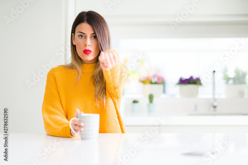 Photo  Young beautiful woman drinking a cup of coffee at home pointing with finger to t