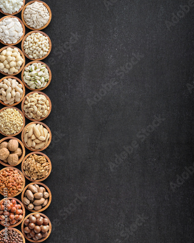 assorted nuts and seeds on black table with copy space, organic food background