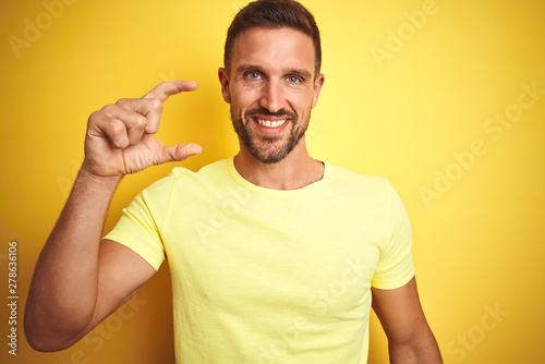 Fotomural  Young handsome man wearing casual yellow t-shirt over yellow isolated background smiling and confident gesturing with hand doing small size sign with fingers looking and the camera