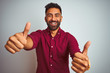 canvas print picture - Young indian man wearing red elegant shirt standing over isolated grey background approving doing positive gesture with hand, thumbs up smiling and happy for success. Winner gesture.