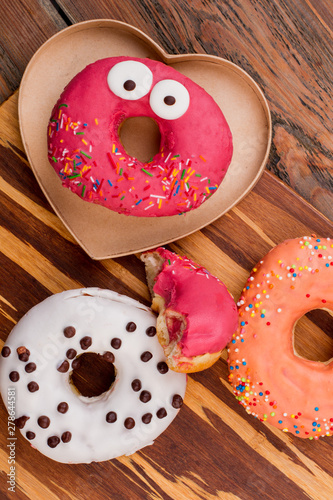 Deurstickers Europa Funny donut on wooden background, top view. Still life of glazed cakes on wooden surface. Funny composition with donuts.