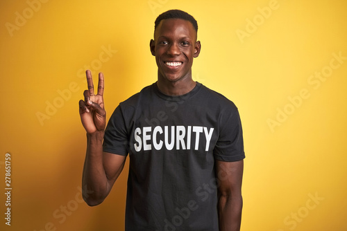 Fototapeta African american safeguard man wearing security uniform over isolated yellow background showing and pointing up with fingers number two while smiling confident and happy. obraz na płótnie