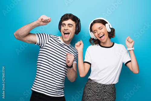excited man and woman dancing while listening music in headphones on blue background - 278653704