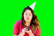 canvas print picture - Woman blowing out her birthday candle on a chocolate cupcake on green screen