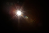 Fototapeta Tęcza - Lens Flare. Light over black background. Easy to add overlay or screen filter over photos. Abstract sun burst with digital lens flare background. Gleams rounded and hexagonal shapes, rainbow halo.