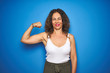 Middle age senior woman with curly hair standing over blue isolated background Strong person showing arm muscle, confident and proud of power