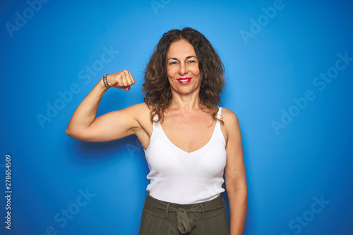 Fotografie, Obraz  Middle age senior woman with curly hair standing over blue isolated background S
