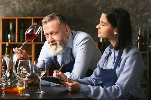 Stampa su Tela Mature sommelier with his student in wine cellar