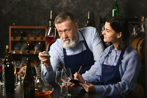 Foto Mature sommelier with his student in wine cellar