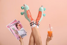 Woman In Vintage Roller Skates, With Fashion Magazines And Juice On Color Background