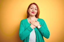 Youg Beautiful Redhead Woman Wearing Winter Green Sweater Over Isolated Yellow Background Smiling With Hands On Chest With Closed Eyes And Grateful Gesture On Face. Health Concept.