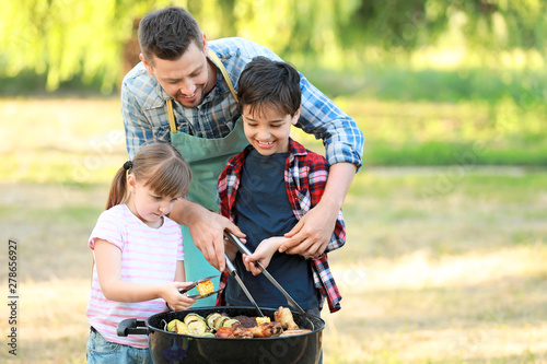 Fototapeta Little children with father cooking tasty food on barbecue grill outdoors obraz