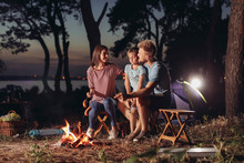 Family Roasting Sausages Over Campfire In Evening