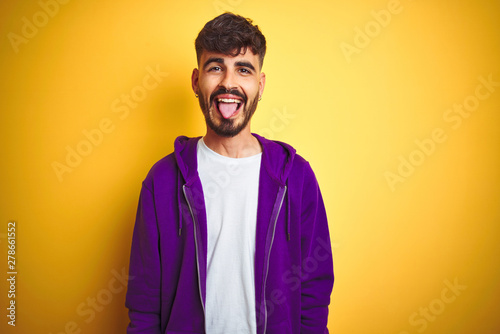 Fototapeta Young man with tattoo wearing sport purple sweatshirt over isolated yellow background sticking tongue out happy with funny expression. Emotion concept. obraz na płótnie