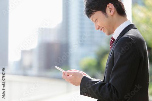 Valokuva スマートフォンを見るビジネスマン