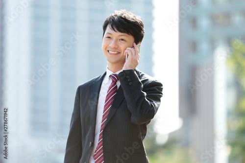 Obraz スマートフォンで通話するビジネスマン - fototapety do salonu