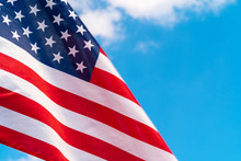 American Flag Waving In The Wind Against Blue Sky