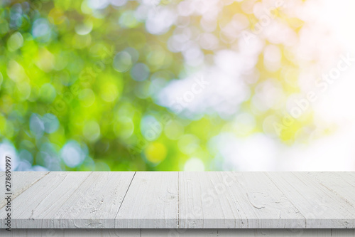 Foto auf AluDibond London Empty wooden table and abstract blurred green bokeh leaves background texture, display montage with copy space.