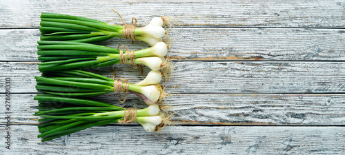 Foto Green onion on a white wooden background