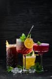 Fototapeta Kawa jest smaczna - Beautiful colorful cocktails in the glasses on the bar.