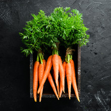 Fresh Carrots On A Black Stone Background. Top View. Free Space For Your Text.