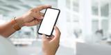 Fototapeta Kawa jest smaczna - Man hands holding blank screen smartphone with blurred background..