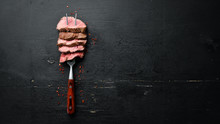 Beef Steak On A Fork. On A Wooden Background. Top View. Free Space For Your Text.