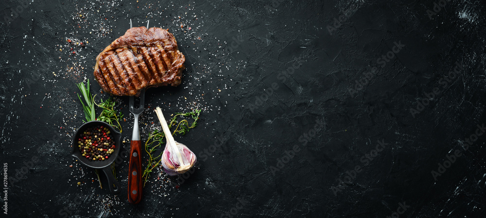 Fototapety, obrazy: Grilled ribeye beef steak on the fork. At the aged table. Top view. Free space for your text.