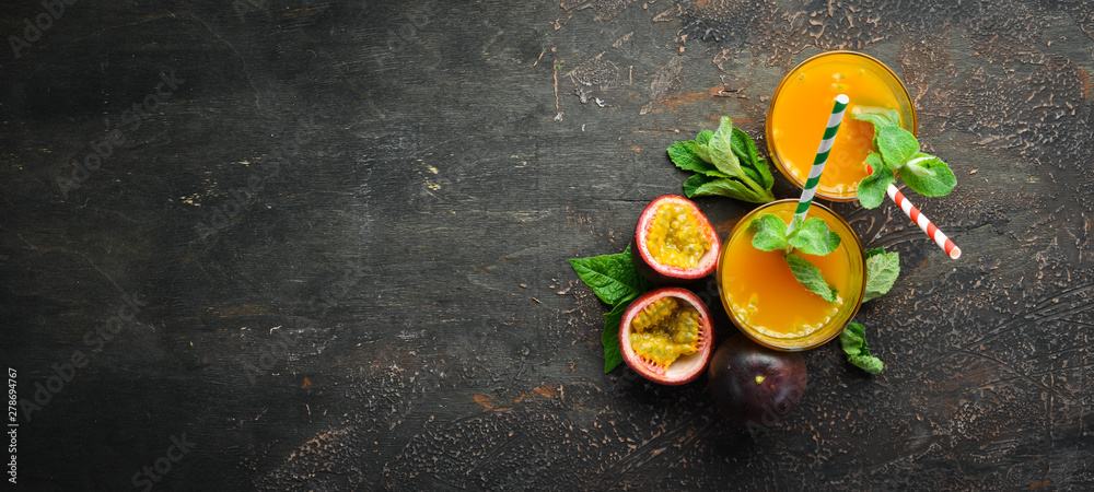 Fototapeta Passion fruits juice and fruits on a wooden background. Tropical Fruits.