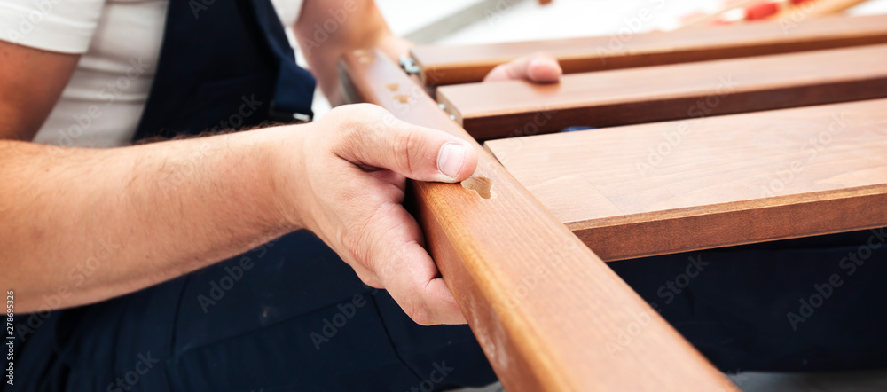Fototapety, obrazy: The man is assembling wooden furniture in home