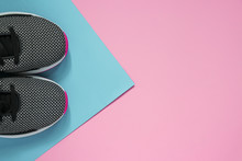 A Pair Of Sport Shoes On Multiclored Surface. New Black And White Woman Sneakers On Pink And Blue Pastel Background With Copy Space. Top View, Flat Lay
