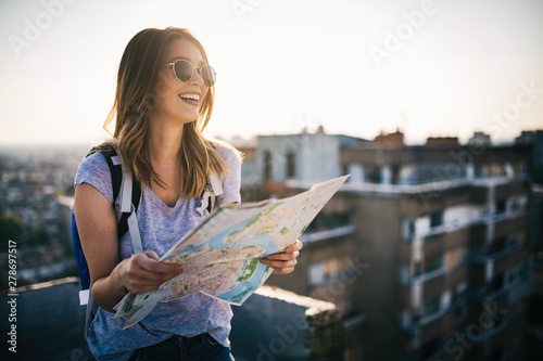 Fototapeta Happy young woman with a city map and a backpack travelling obraz