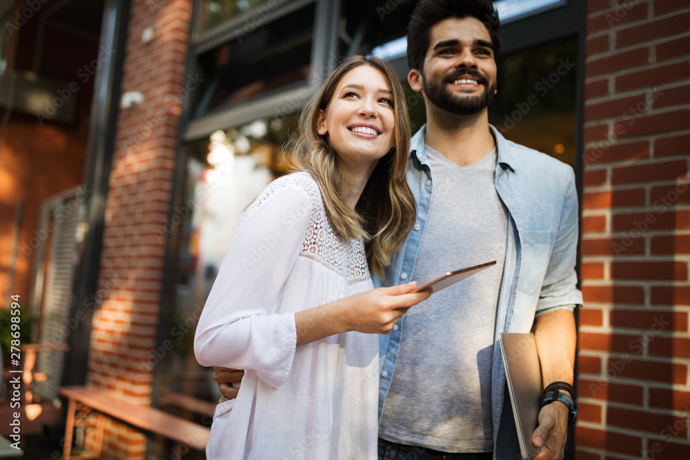 Fototapety, obrazy: Young couple using a digital tablet together and smiling