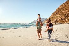 Mid Adult White Couple Walking Along On A Beach On A Family Holiday Carrying Their Kids, Full Length