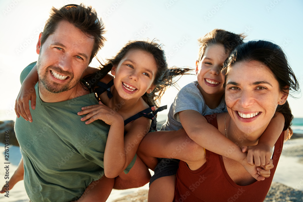 Fototapety, obrazy: Mid adult white parents piggybacking their kids on a beach, smiling to camera, close up, backlit
