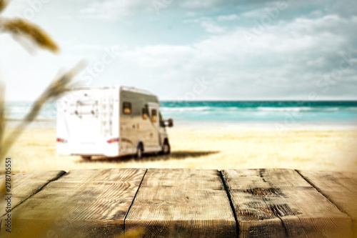 Fototapeta Table background with a wooden board and sunny beach and ocean and a camper van
