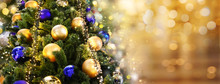 Christmas Tree Decorated With Golden And Blue Balls Toys On A Blurred, Sparkling And Fabulous Fairy Background With Beautiful Bokeh, Copy Space, Banner Format.