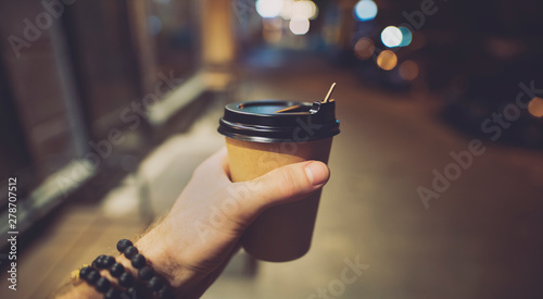 POV, coffee or latte paper cup in a male hand at night - 278707512