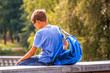 Tired kid with backpack sitting outdoors after school