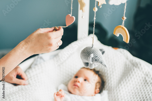 Obraz Adorable two month old baby girl lying on the bad. Mother standing near the cradle and holding clack. Concept photo parenthood and motherhood. - fototapety do salonu