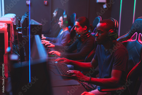 Fotografija  Group of busy multi-ethnic online gamers in casual outfits sitting at table and